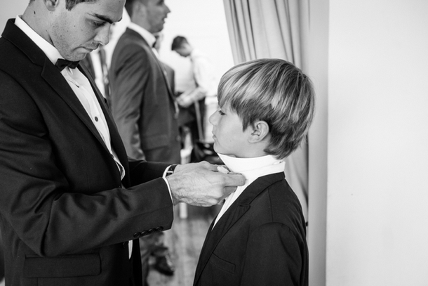 Groom Tying Bowtie for Page Boy | Credit: Lad & Lass
