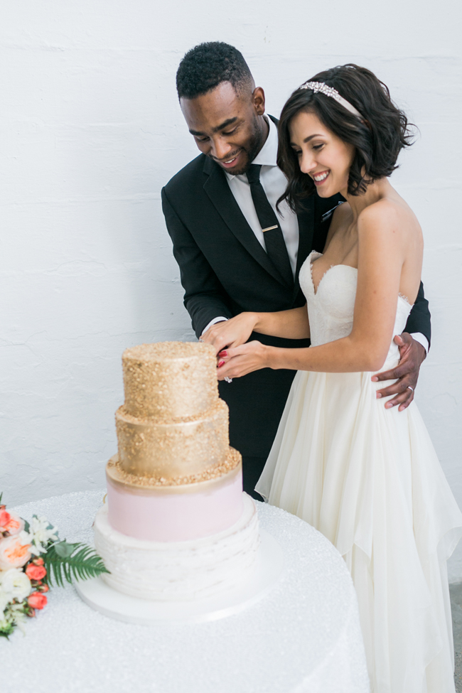 bride and groom with gold wedding cake | SouthBound Bride | Credit: Alexis June Weddings