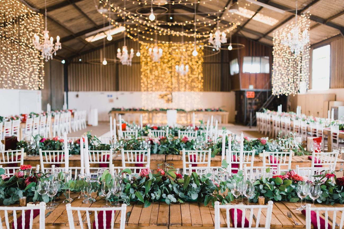 Barn wedding reception with twinkle light curtains | Credit: Matthew Carr