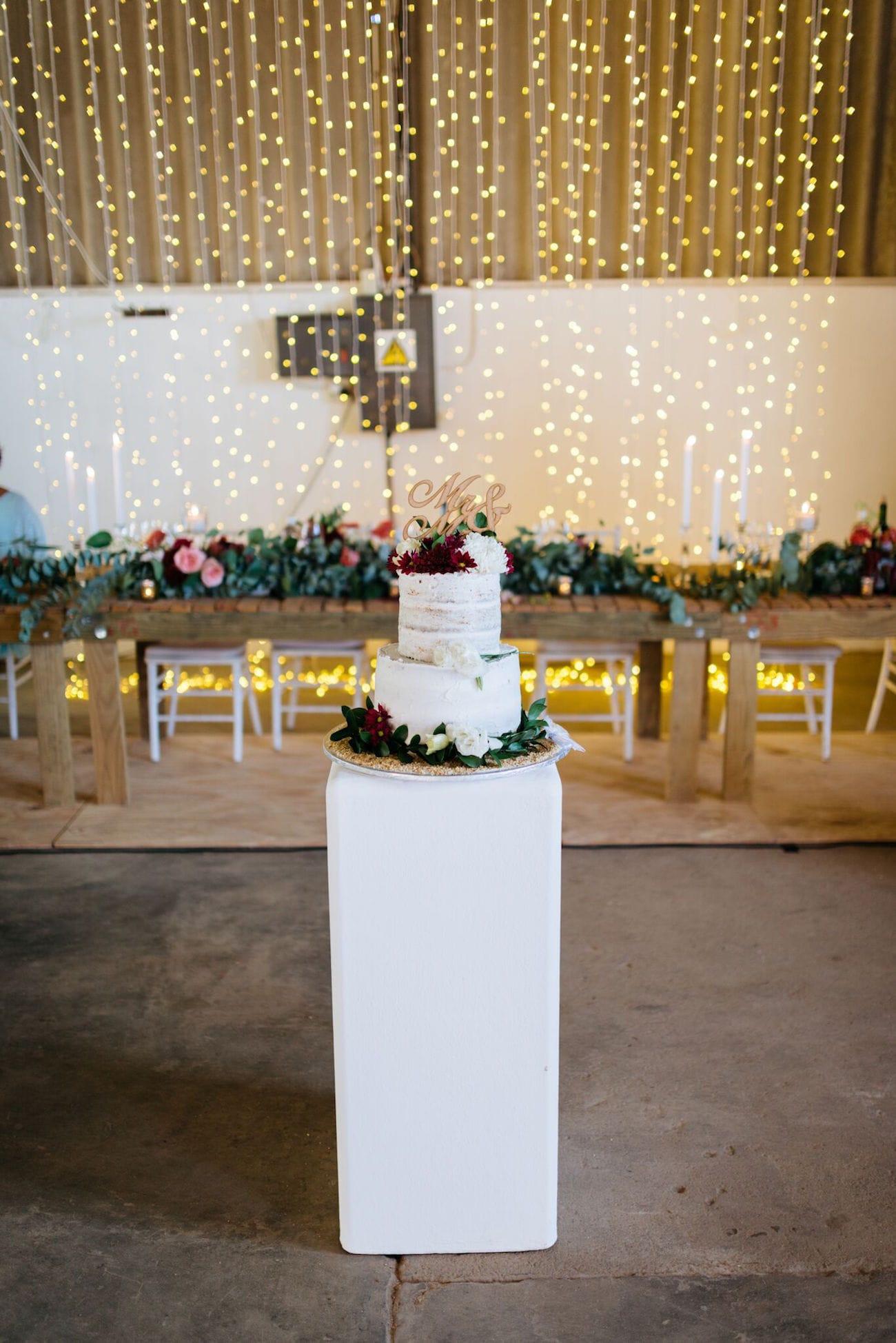 Semi-naked wedding cake with twinkle light backdrop | Credit: Matthew Carr