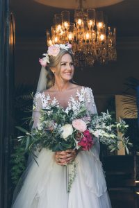 Bride with handtied bouquet and floral crown | Credit: Shanna Jones