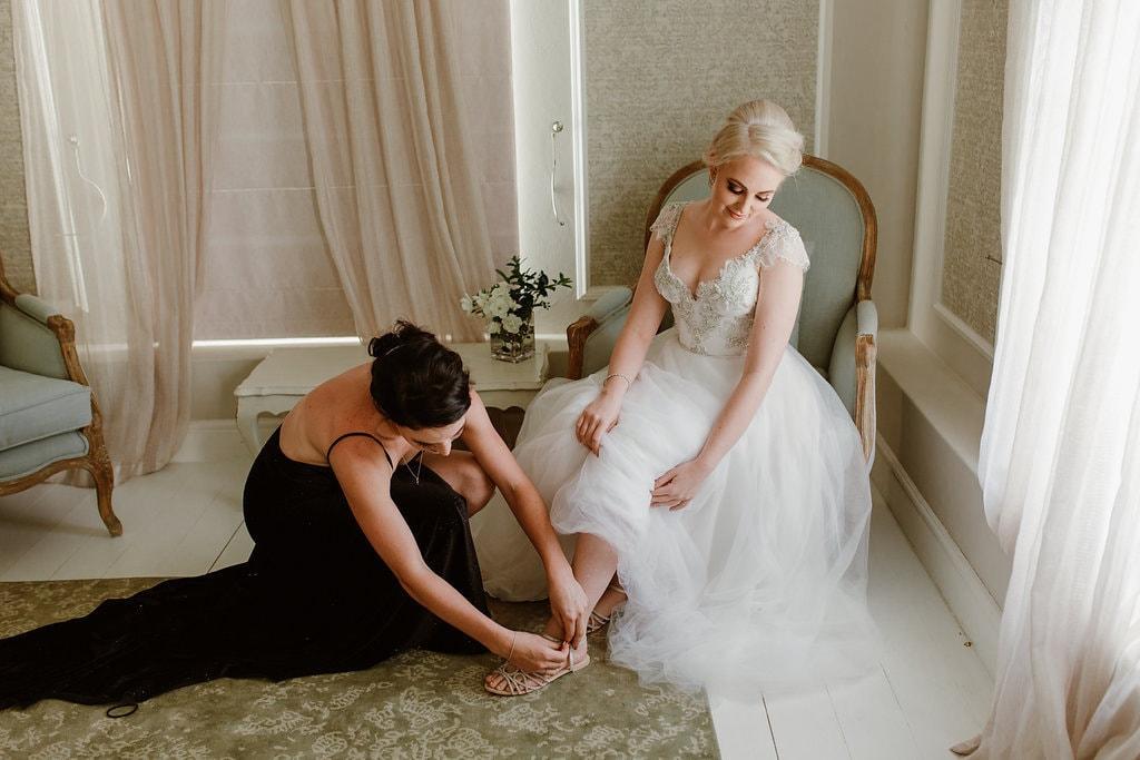 Bridesmaid Helping Bride with Shoe | Image: Jenni Elizabeth