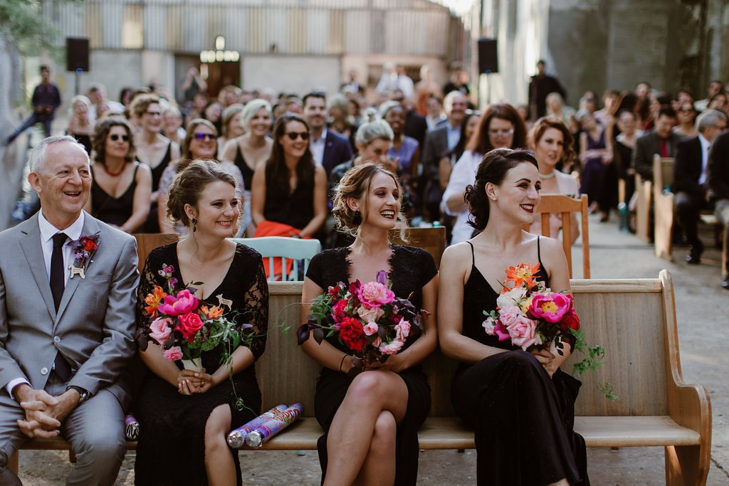 Bridesmaids in Black Dresses with Bold Bouquets | Image: Jenni Elizabeth