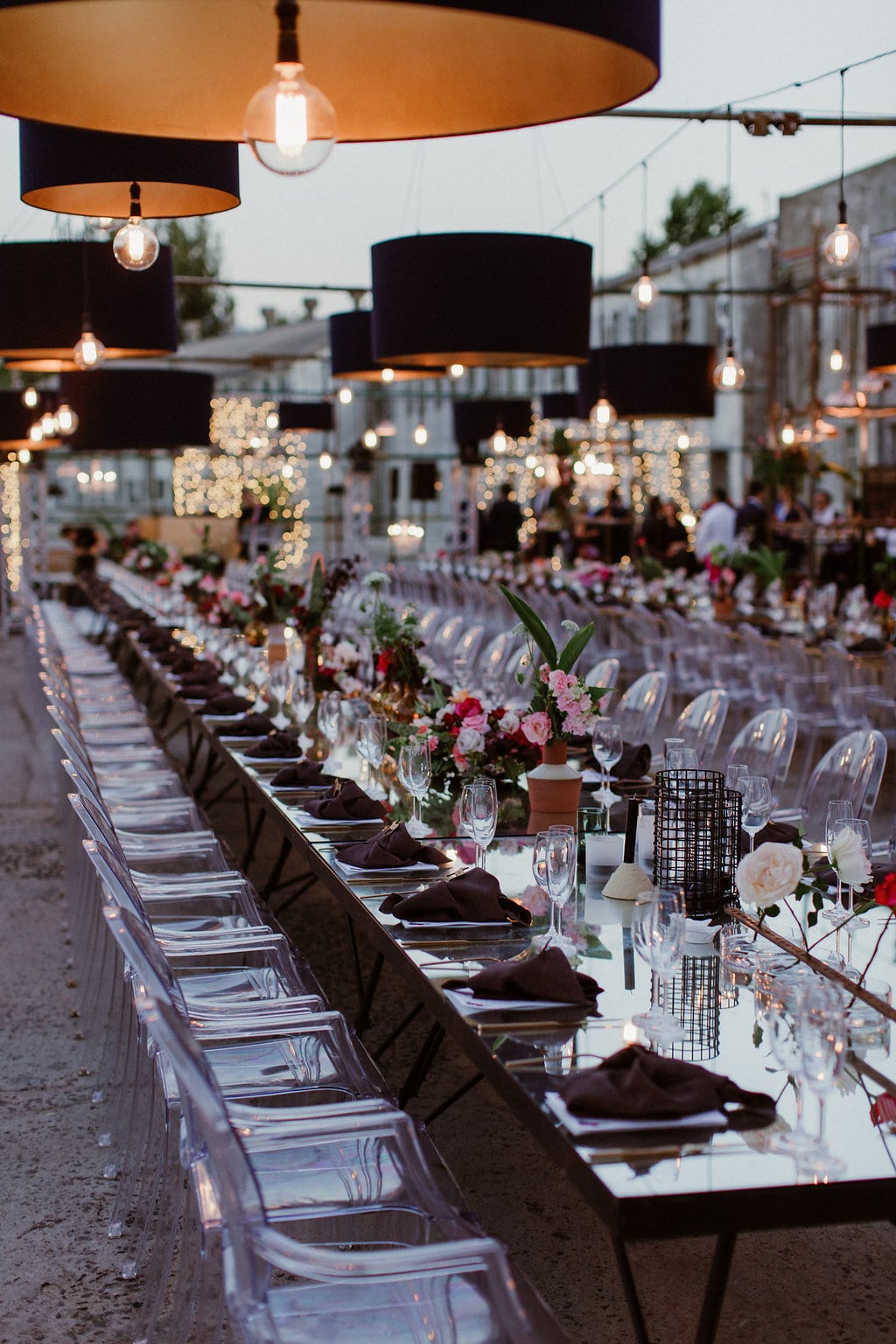Long Glass Tables with Ghost Chairs and Hanging Lights | Image: Jenni Elizabeth